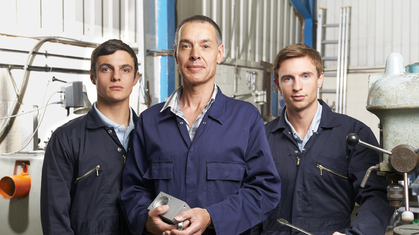 Three manufacturer workers stand in their workplace